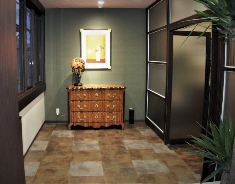 グリーン色の壁面にセオドアアレキサンダー社のチェストが置かれたエントランス