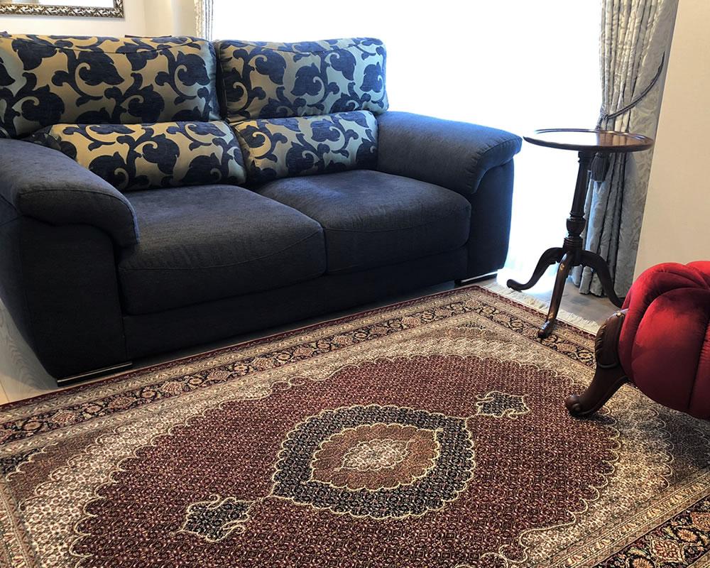 ダークブルーのソファと赤いペルシャ絨毯