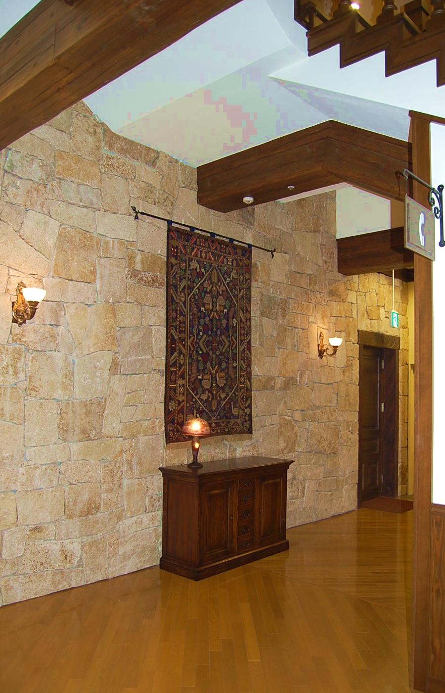 石の壁面に絨毯を飾り、サイドボードをその下に配置。