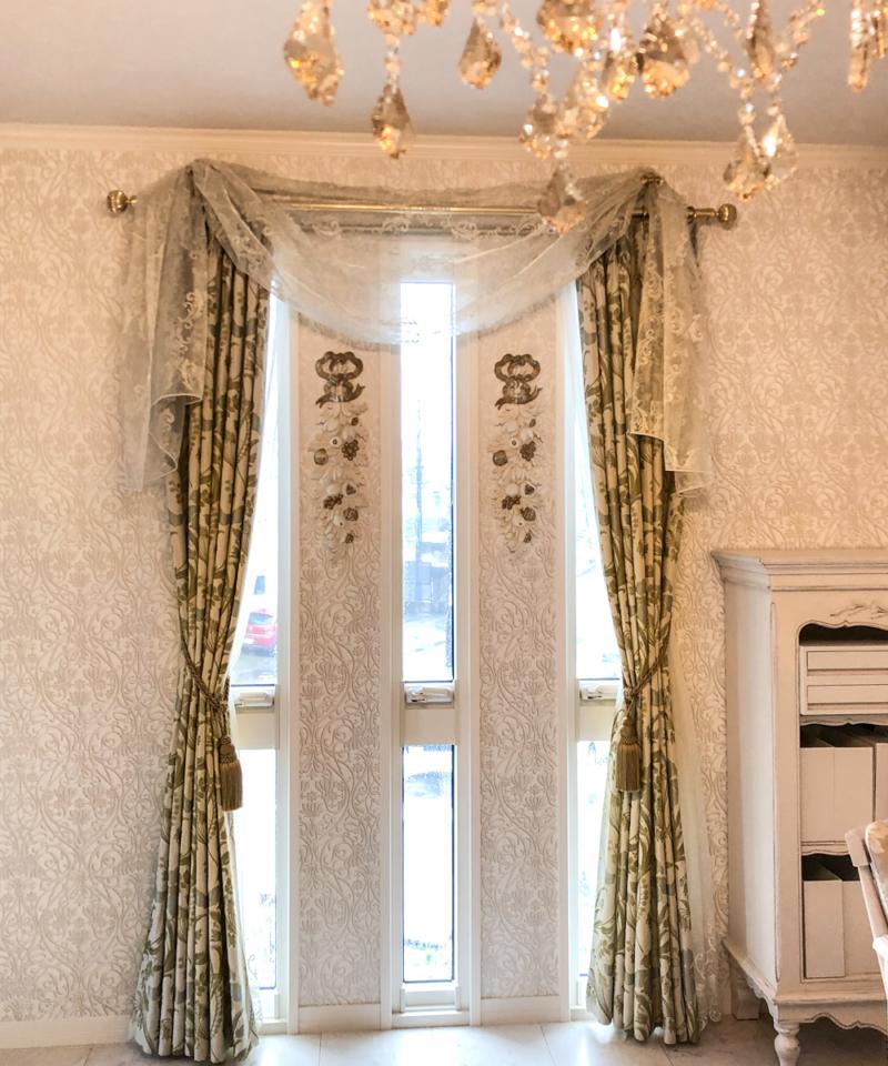 シャンデリアにマントルピース、装飾カーテンが美しい